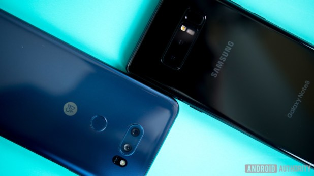 The LG V30 and Galaxy Note 8 smartphones, face-down on a turquoise surface.