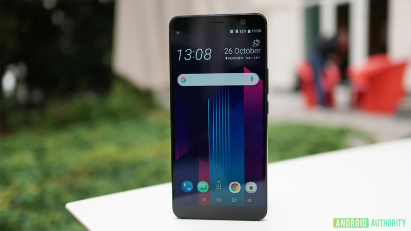 Photo of the front side of HTC U11 Plus in an upright position with a grass background.