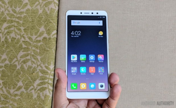 Xiaomi Redim Y2 smartphone in white, in someone's hand, in front of curtains.