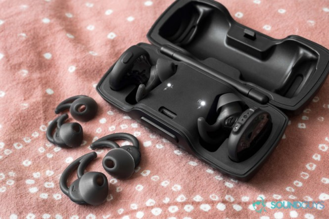 Best workout earbuds: The Bose SoundSport Free in the case with the extra StayHear+ ear tips on a pink comforter.