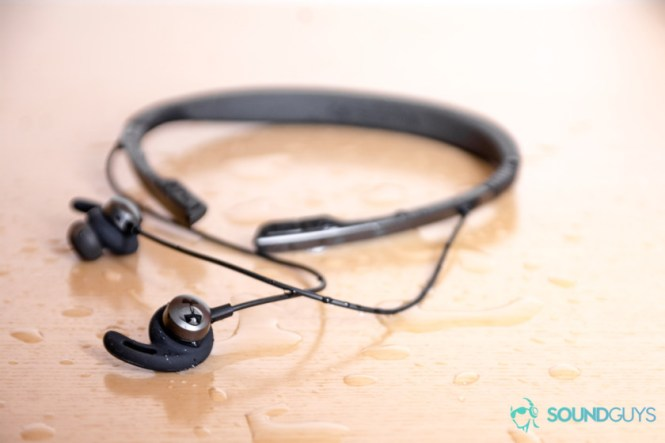 Best workout earbuds: The Under Armour Sport Flex Wireless by JBL on a light wood table with water droplets on and around the earbuds.