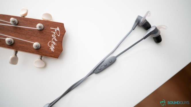Best workout earbuds: Jaybird X4 earbuds on a white table with part of a ukulele in teh background.