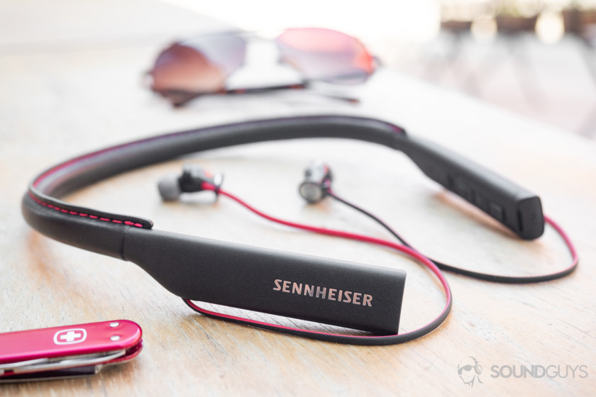 Are Beats worth it? Sennheiser HD1 In-Ear Wireless earbuds on a wooden table with a Swiss Army Knife in the foreground and sunglasses in the background.