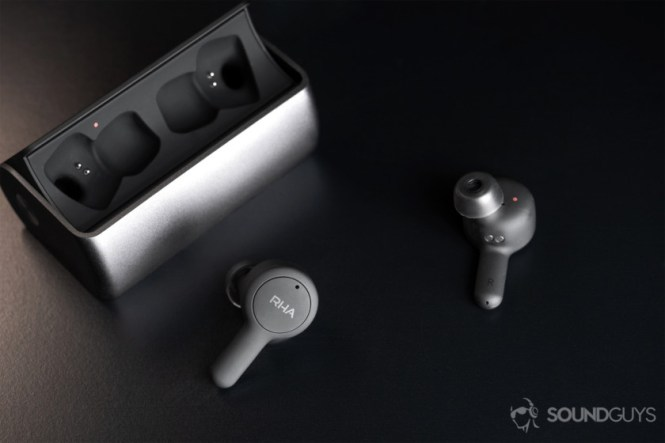 RHA TrueConnect: Angled downward image of the open charging case with the earbuds facing the lens in different directions; the closer 'bud shows the RHA logo.