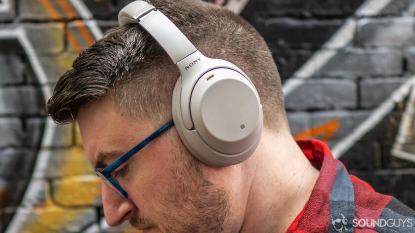 A photo of a man wearing wireless headphones.
