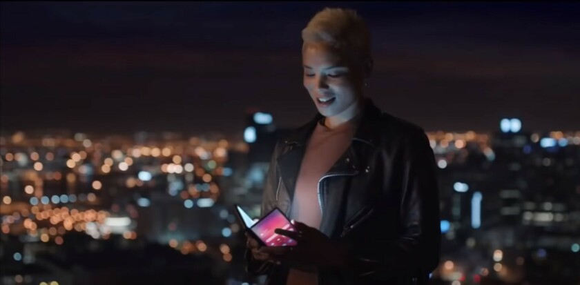 A woman holding a folding phone in front of a city at night.