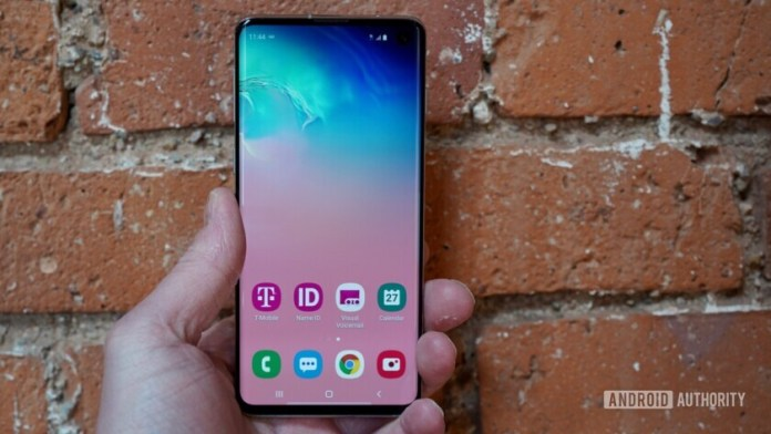 Front side of the Samsung Galaxy S10 held in hand with the display turned on.