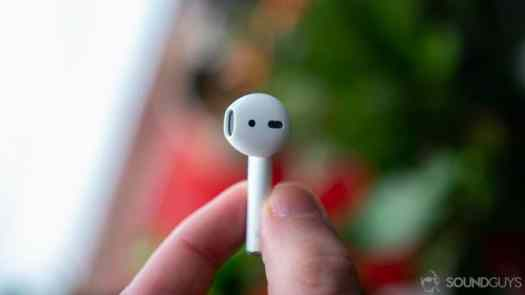 Apple's new AirPods with the right earbud between a man's fingers.