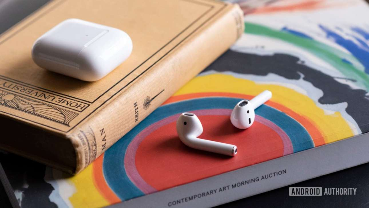 Apple новые AirPods 2 вне футляра опираются на книгу.