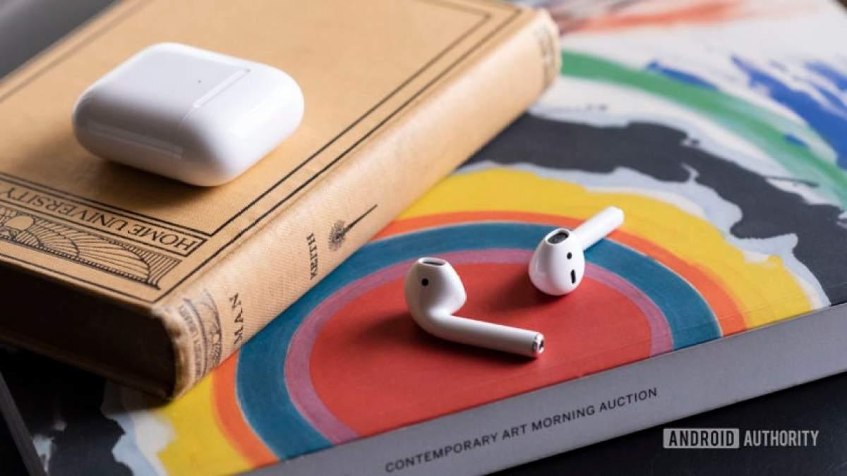 Os novos AirPods 2 da Apple fora da caixa, apoiados em um livro.