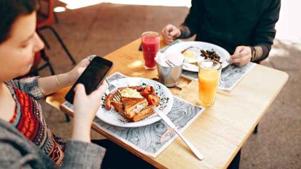An image of two people dining out with one using Google Maps on their smartphone to photograph a popular dish.