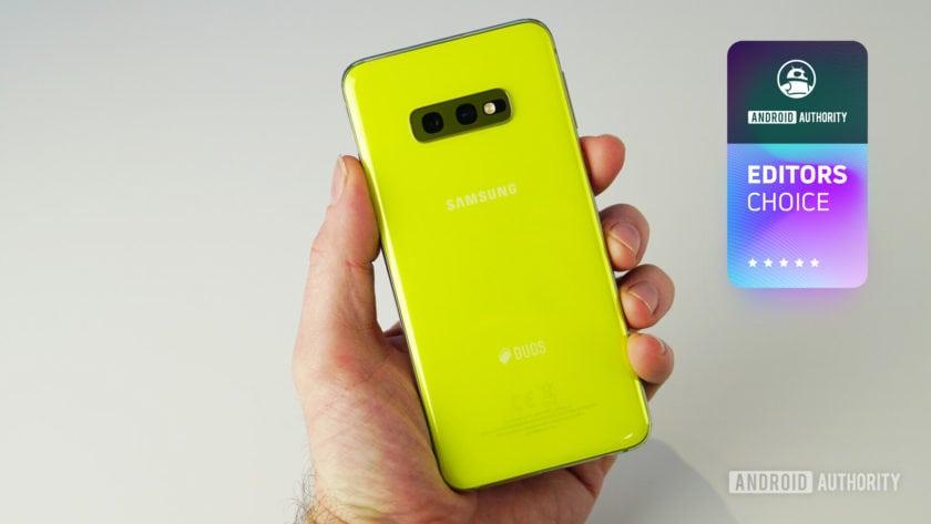 Желтый Samsung Galaxy S10e держится в левой руке человека.