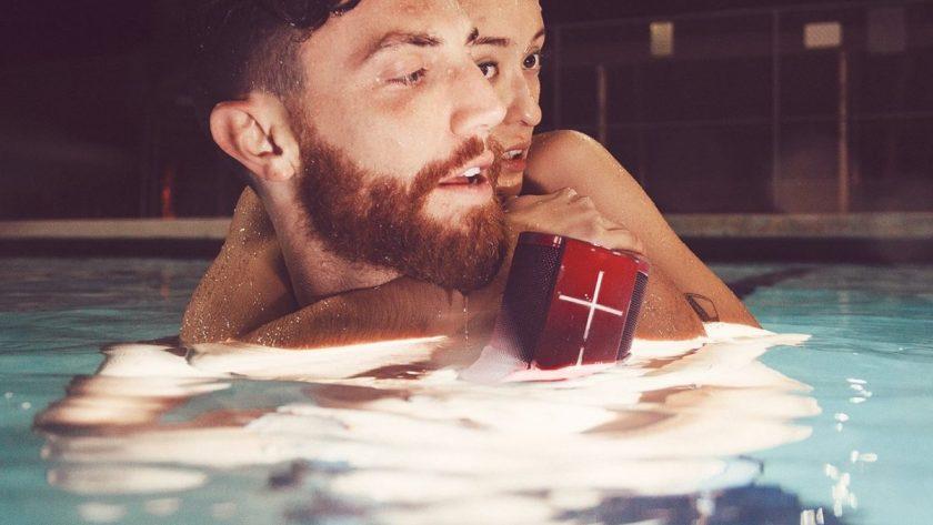 UE Megablast Alexa smart speaker man holding it in pool