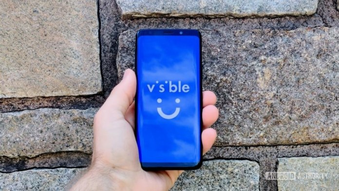 A Samsung Galaxy S9 in front of a brick wall with the Visible logo on the display.