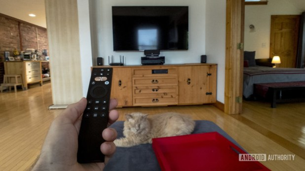 A first-person view of a man sitting on a couch with a Caavo Universal Remote in his hand.