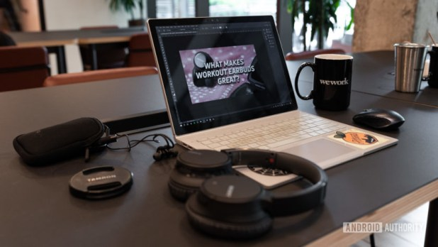 A laptop with Photoshop open and a set of Sony ANC headphones with a ceramic mug in the background.
