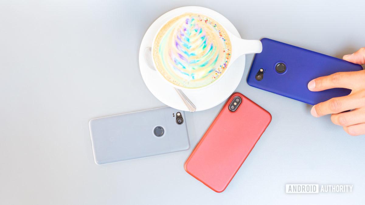 Смартфоны на столе рядом с красочным кофе.  Продажа телефонов в магазине.