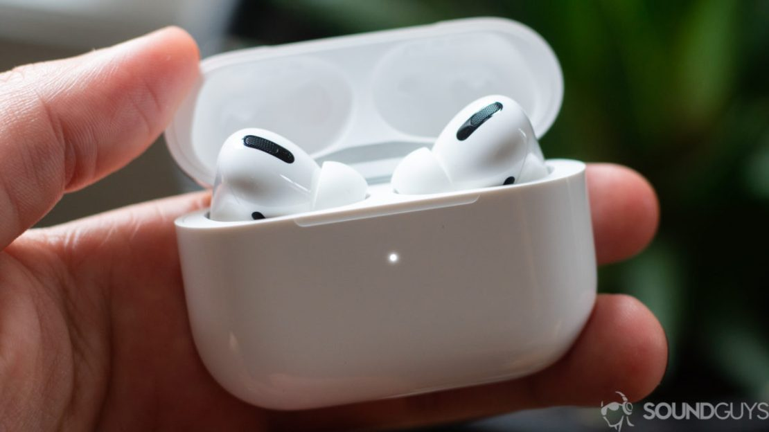 The Apple AirPods Pro earbuds charging case in a man's hand.