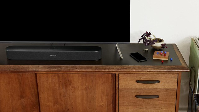 A picture of the Sonos Beam soundbar in black on a TV stand.