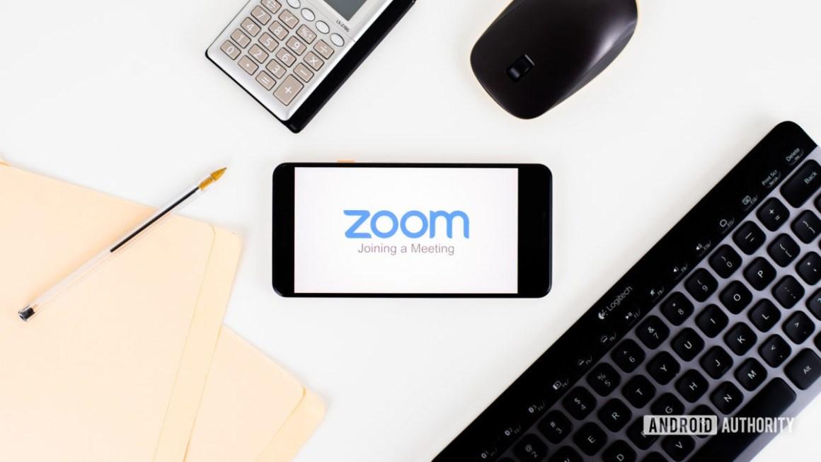 Zoom Meetings на смартфоне рядом с офисным оборудованием 1
