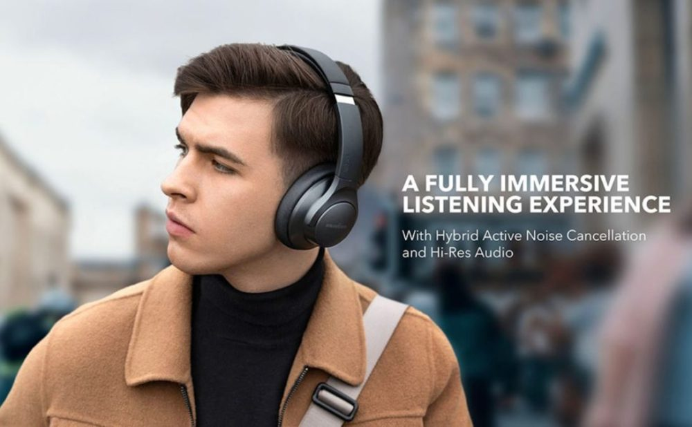A man wears Bluetooth headphones overriding the cheap sound of the Anchor Soundcore Life Q20.