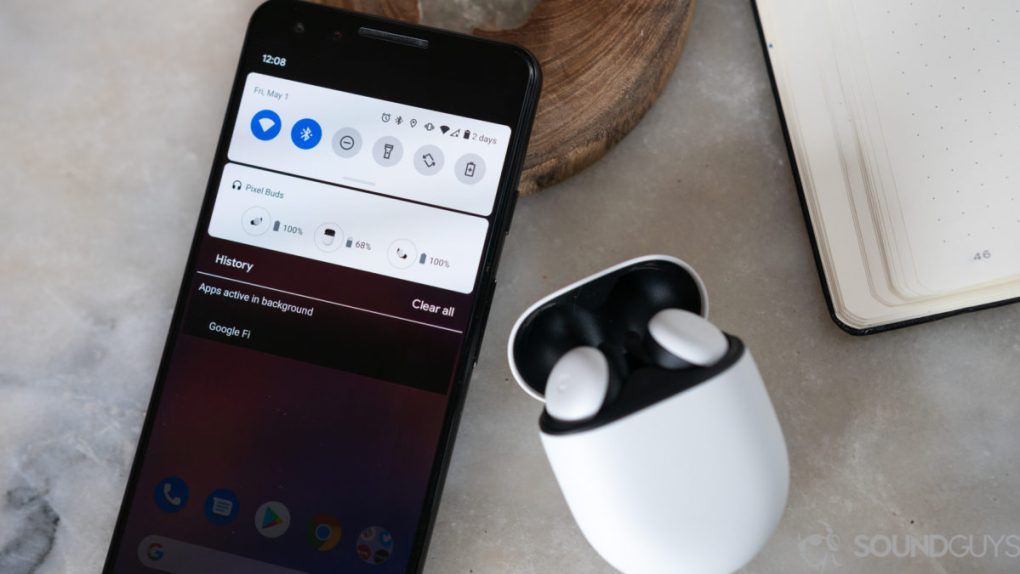 The Google Pixel Buds 2020 true wireless earbuds case open and next to a Pixel smartphone with the Bluetooth dropdown menu displayed.