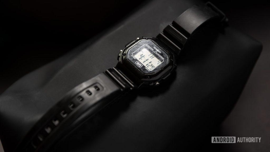 Изображение черных часов Casio F108WH Illuminator на черной поверхности.