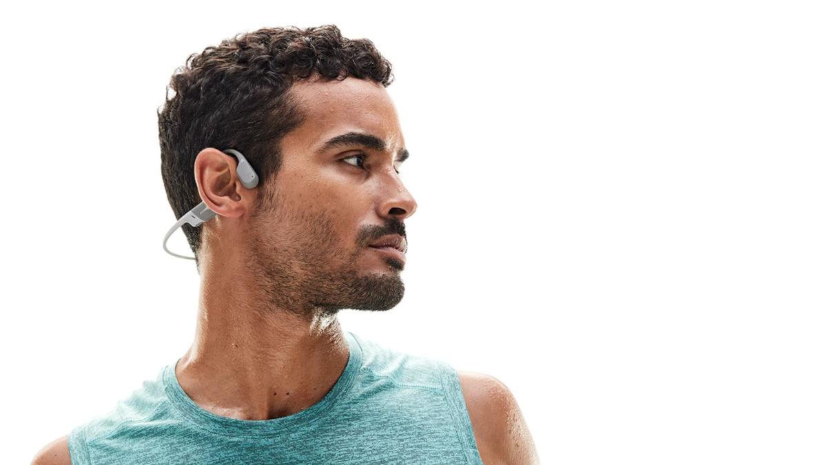 Фотография мужчины в профиль в наушниках для костной проводимости AfterShokz Aeropex.