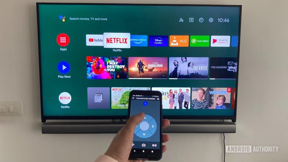 Изображение, показывающее приложение дистанционного управления Android TV на смартфоне перед телевизором Android