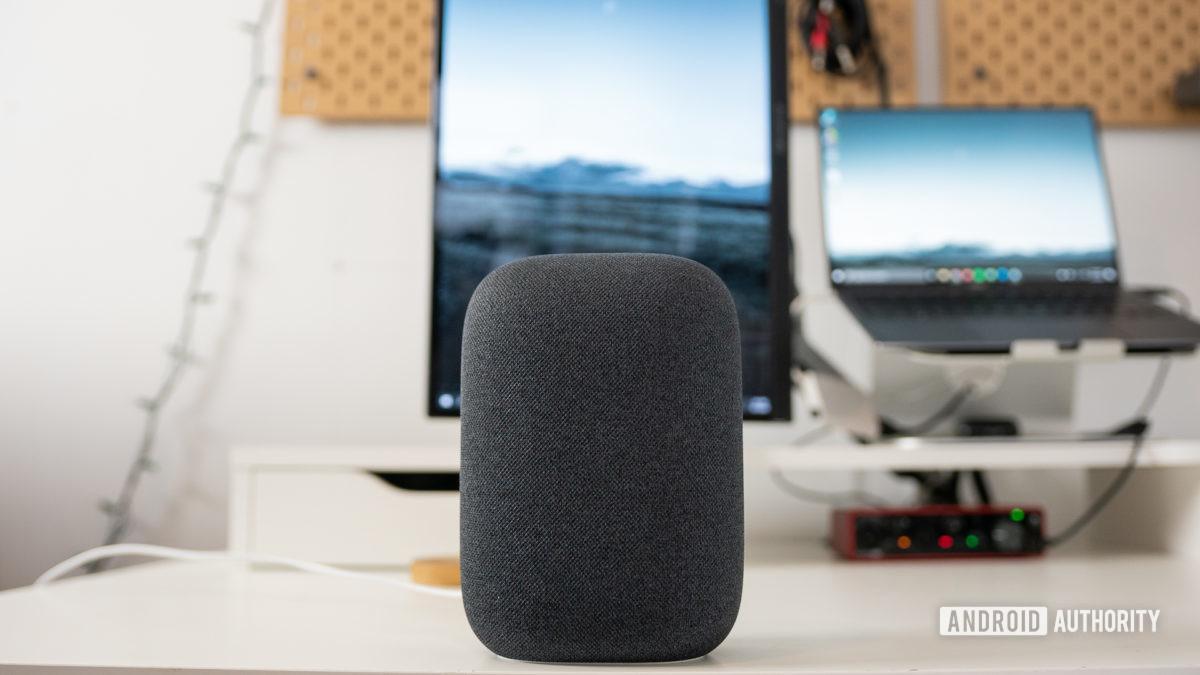Серый динамик Google Nest Audio на белом столе перед экранами компьютеров.