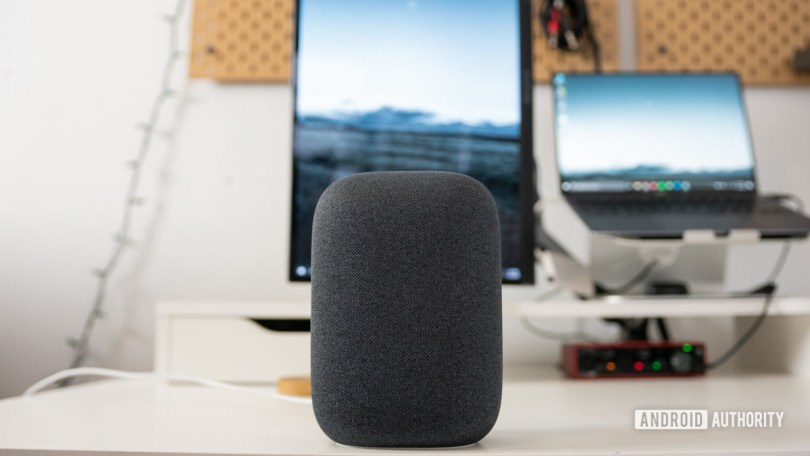 The gray Google Nest Audio speaker pictured on a white desk in front of computer screens.
