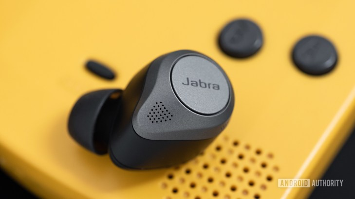 The Jabra Elite 85t noise cancelling true wireless earbuds microphone holes next to a Gameboy Color speaker grill.