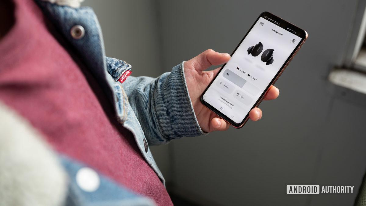 Uma mulher usa o aplicativo móvel Bose Sport Earbuds de verdadeiros fones de ouvido de treino sem fio, o aplicativo Bose Music.