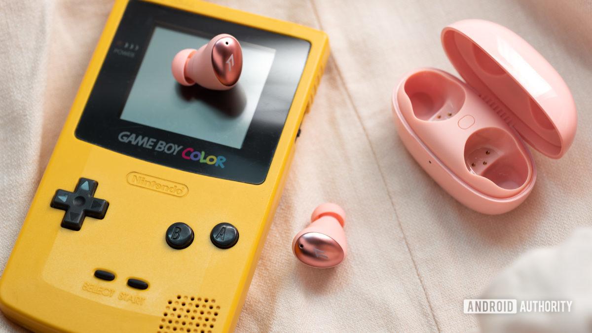 O 1MORE ColorBuds em rosa contra um GameBoy Color em amarelo.
