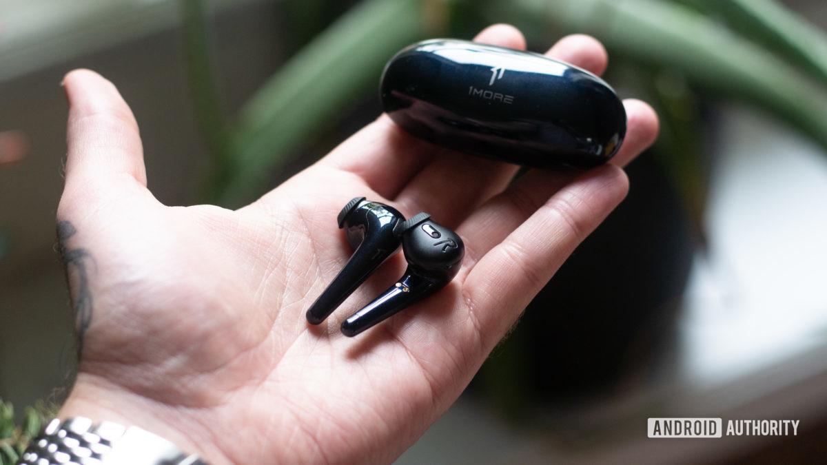 Uma mão segura os fones de ouvido sem fio verdadeiros 1MORE Comfobuds e o estojo de carregamento.