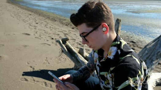 A man is seated at the beach with a smartphone and wearing Google Pixel Buds A-Series.