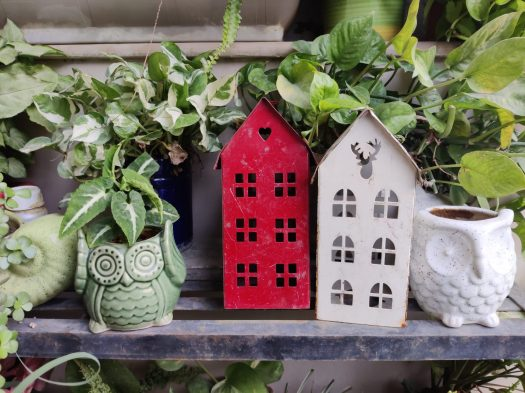 The OnePlus Nord outdoor primary shot showing red and white house planters, a white owl planter, and a green owl planter.