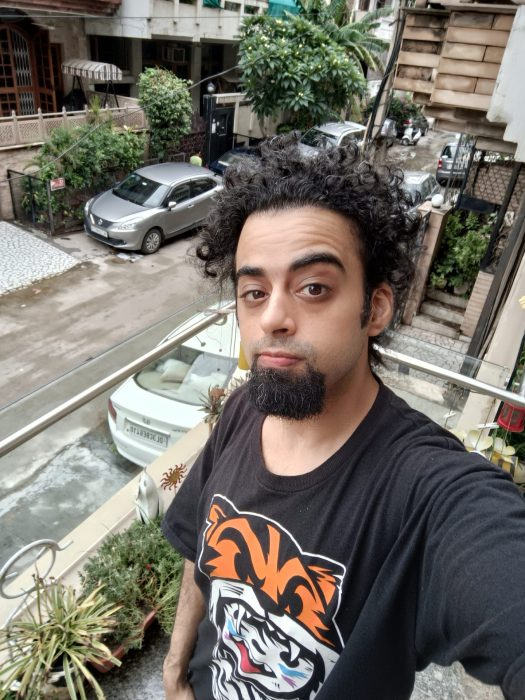 The Oppo Reno 6 Pro selfie standard showing a man with black hair and beard in a black t-shirt with orange pattern standing on a balcony above the street below.