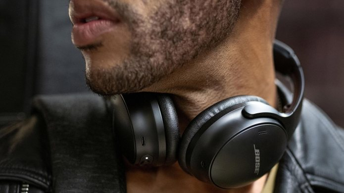 A man wears the Bose QuietComfort 45 noise-cancelling headphones in black around his neck.