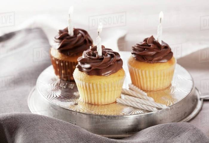 Three Birthday Cupcakes With Lighted Candles Stock Photo Dissolve