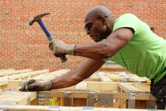 Black man hammering nail at construction site - Stock Photo - Dissolve