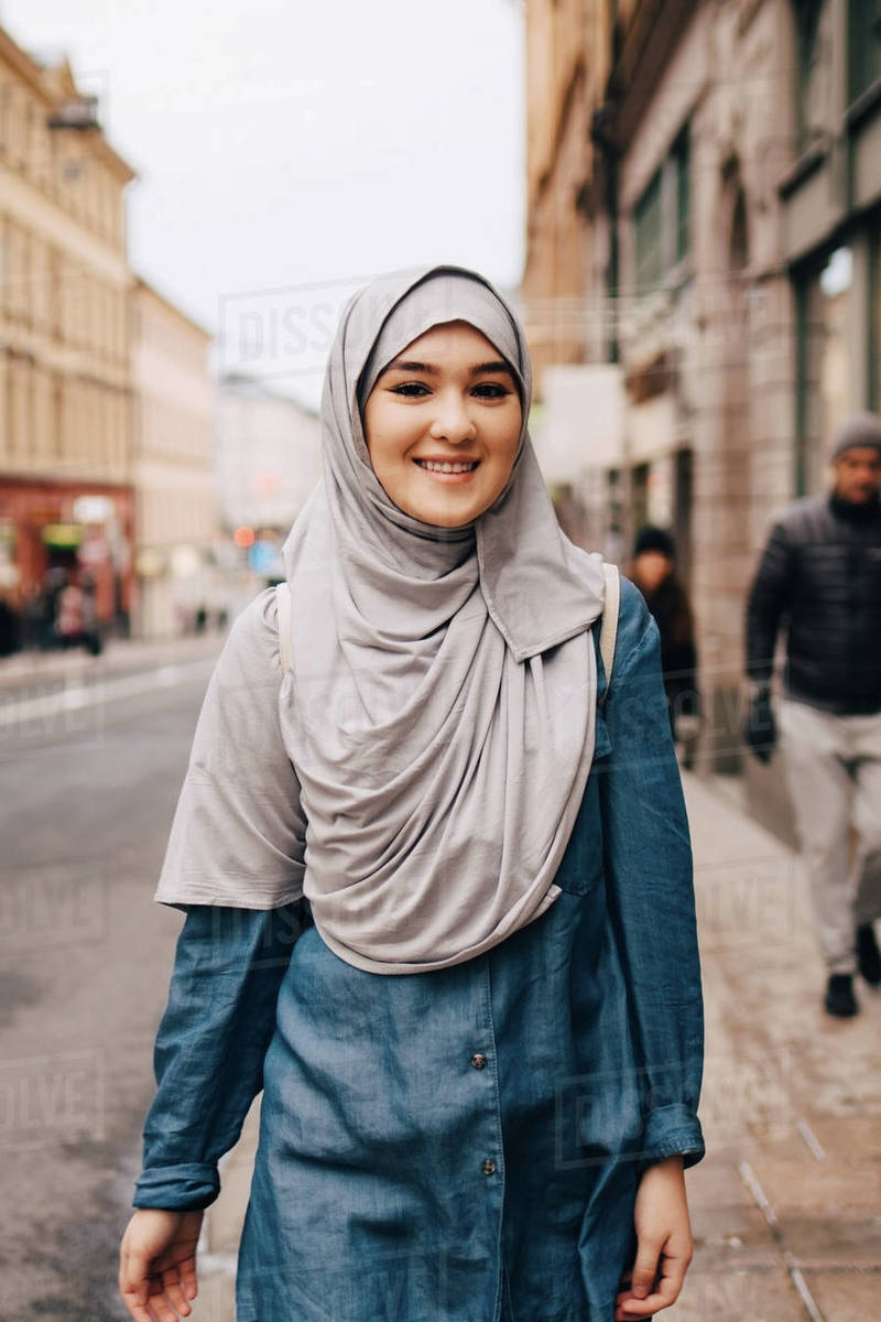 The body needs to adhere to the islamic standards of. Portrait Of Smiling Young Muslim Woman Wearing Hijab Walking On Sidewalk In City Stock Photo Dissolve