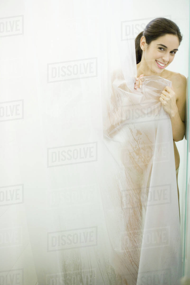 woman peeking out from behind shower curtain smiling at camera d984 32 464