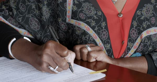 Black senior woman over 50 signing her name on legal paperwork or contracts  with her signature