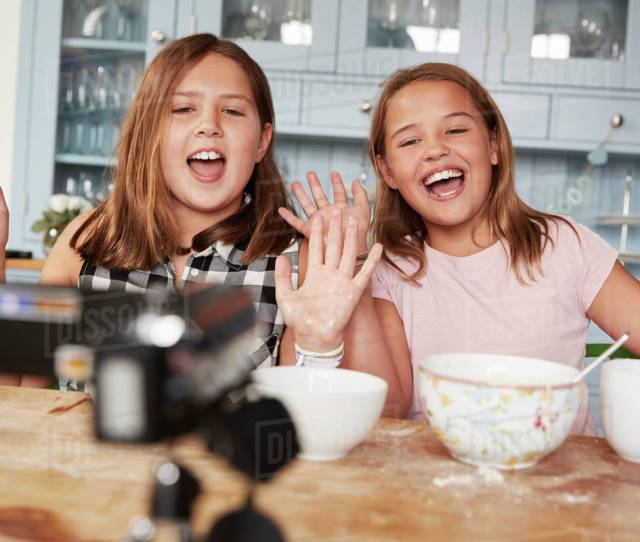 Two Pre Teen Girls Video Blogging In The Kitchen Waving To Camera
