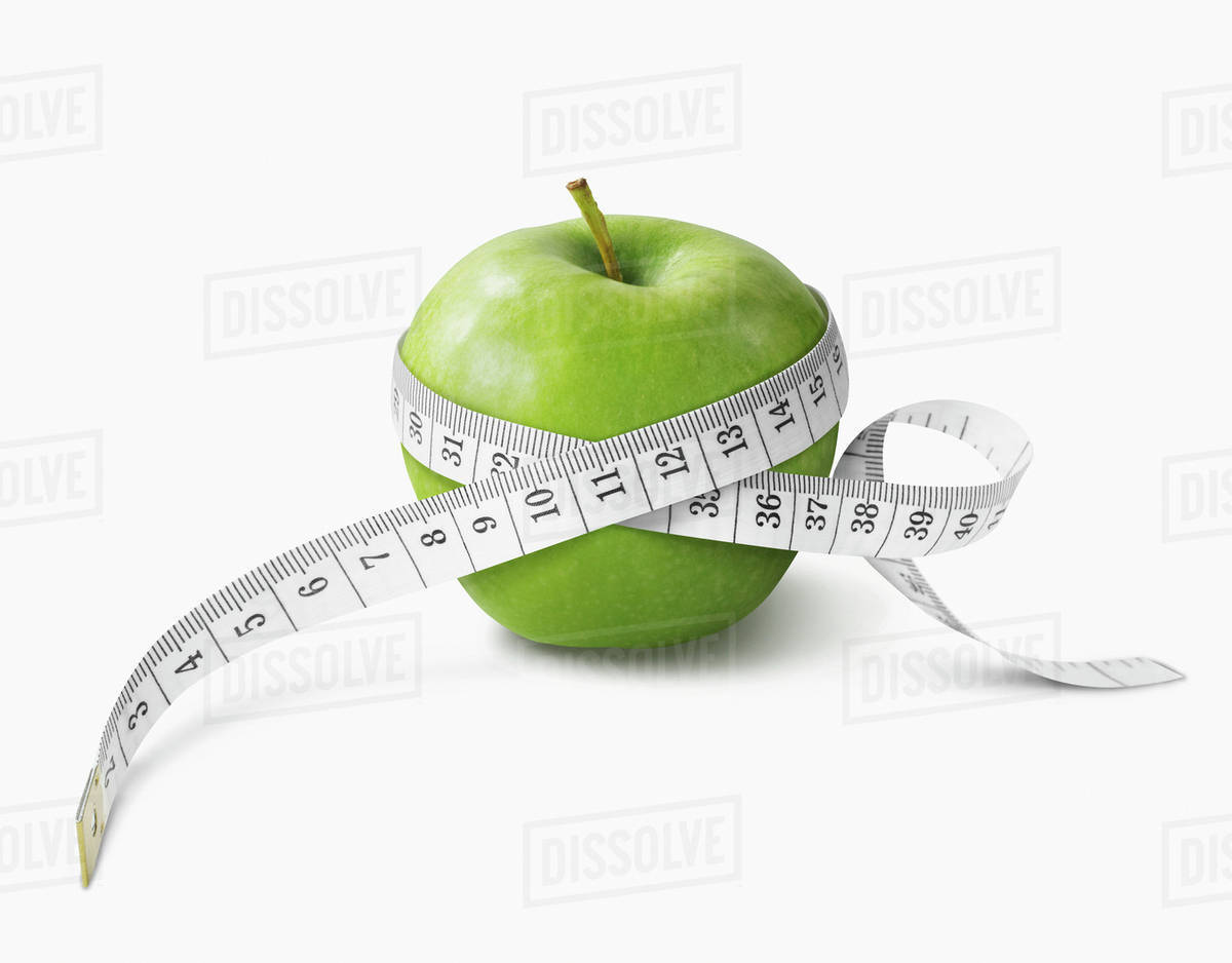 A Measuring Tape Wrapped Around A Green Apple