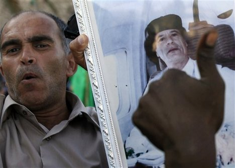 In this photo taken on a government-organized tour, showing a Libyan man holding a Moammar Gadhafi's portrait as he and others rally at the Green Square in central Tripoli, Libya, on Friday, June 24, 2011.