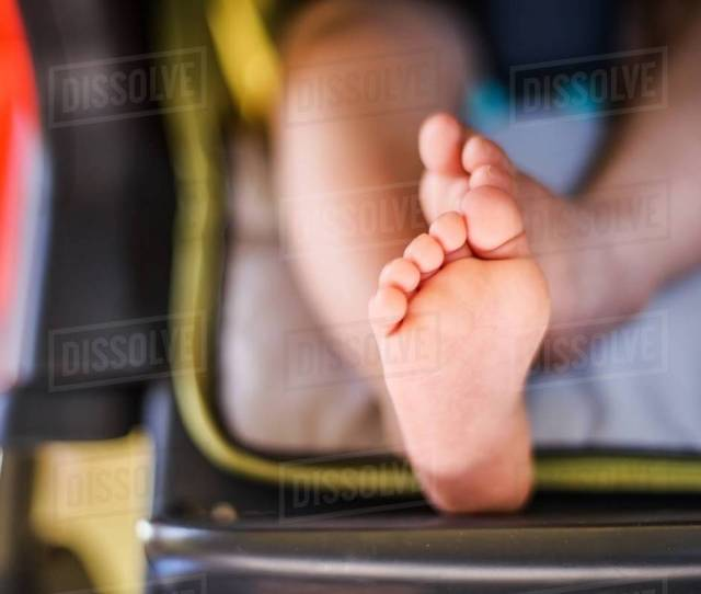 Close Up Of Baby Boys Feet Sitting In High Chair