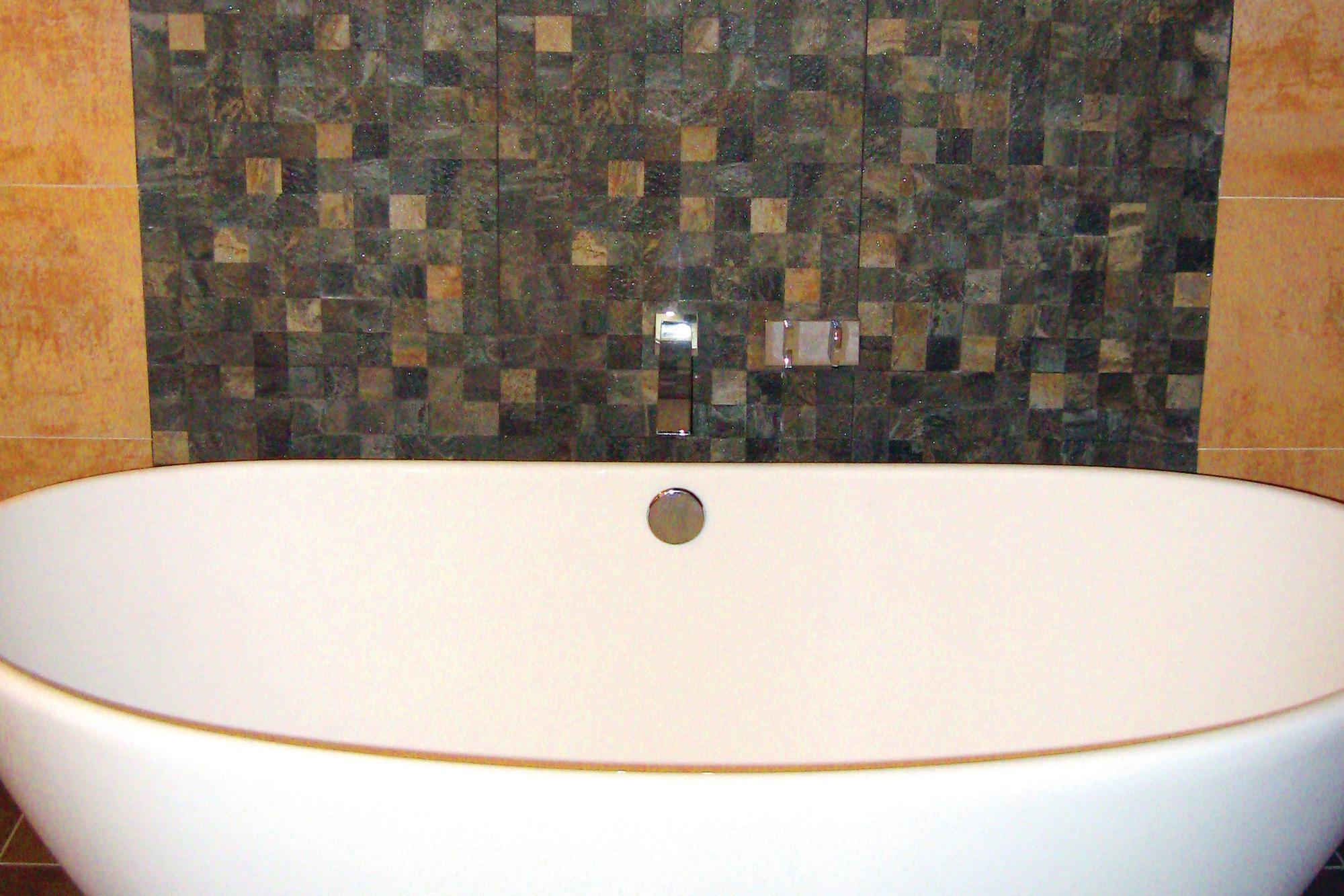 A Textured Backsplash Anchors A Freestanding Tub Builder