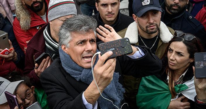 Algerian businessman and political activist Rachid Nekkaz (C) argues with Algerians in front of the Geneva University Hospitals (HUG) buildings in Geneva on March 8, 2019